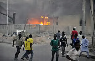 Smoke rises from the police HQ as people run for safety during the recent attacks in Kano.