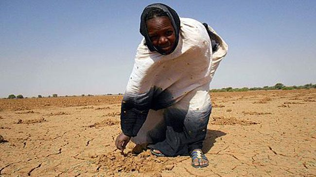 A photo released by Oxfam in December 2011 shows a women pointing at dry land in Mauritania.